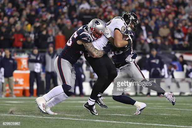 Chris Long of the New England Patriots tackles Dennis Pitta of the Baltimore Ravens during their game at Gillette Stadium on December 12 2016 in...