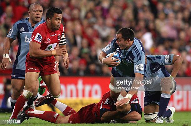 Chris Lowrey of the Blues is tackled during the Super Rugby Semi Final match between the Reds and the Blues at Suncorp Stadium on July 2 2011 in...