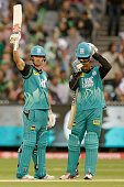 Chris Lynn of the Brisbane Heat raises his bat after scoring 50 runs during the Big Bash League match between the Melbourne Stars and the Brisbane...