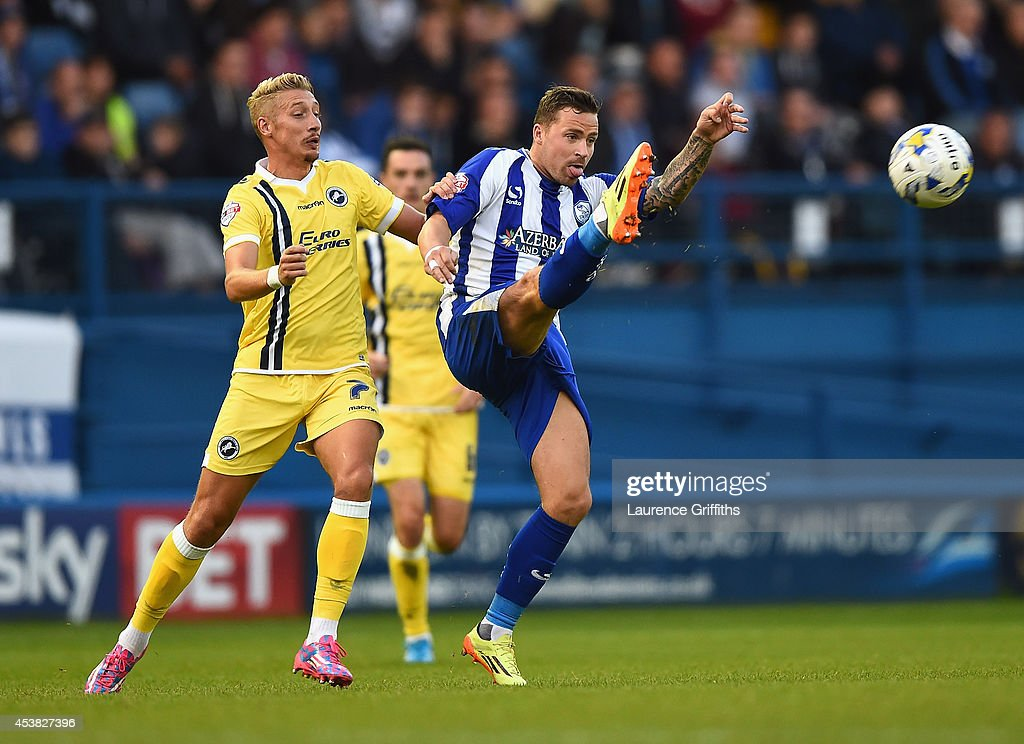 Chris Maguire of Sheffield Wednesday clears from <a gi-track='captionPersonalityLinkClicked' href=/galleries/search?phrase=Lee+Martin+-+Soccer+Player+-+Born+1987&family=editorial&specificpeople=15382346 ng-click='$event.stopPropagation()'>Lee Martin</a> of Millwall during the Sky Bet Championship match between Sheffield Wednesday and Millwall at Hillsborough Stadium on August 19, 2014 in Sheffield, England.