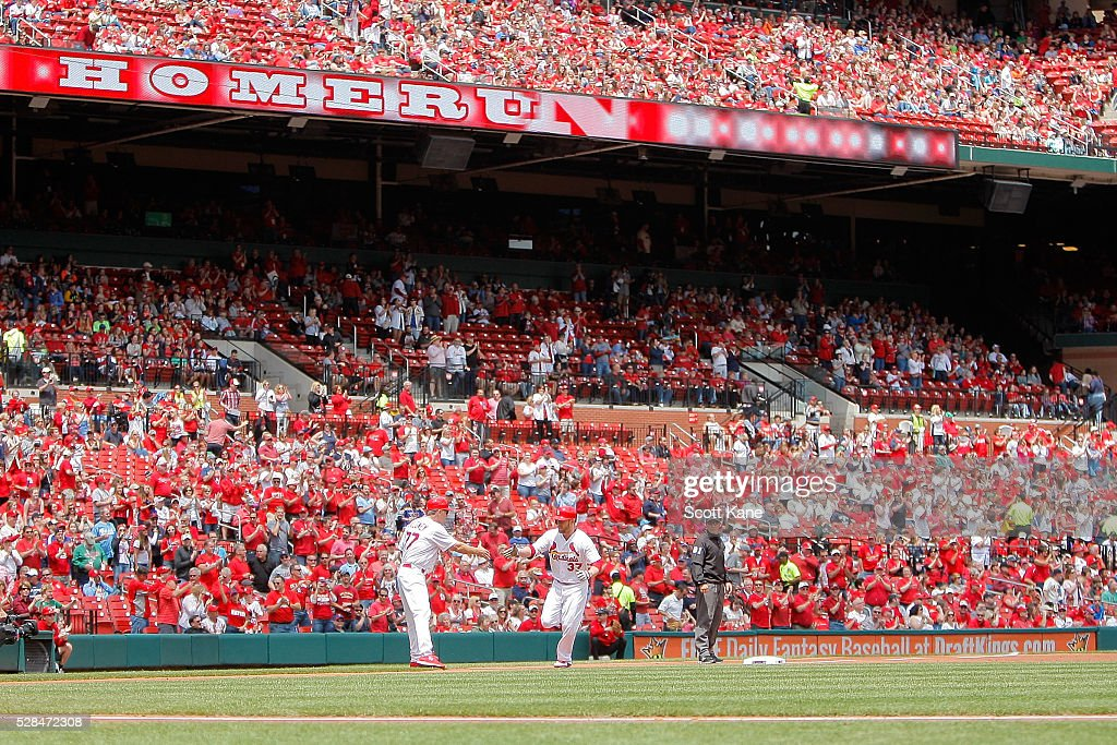 Chris Maloney #77 of the St. Louis Cardinals congratulates Brandon Moss #37 as he runs the bases after hitting a solo home run during the first inning against the Philadelphia Phillies at Busch Stadium on May 5, 2016 in St. Louis, Missouri.