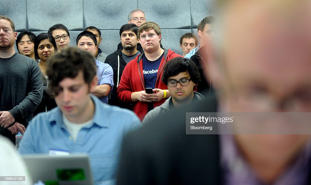 Chris Marra, a Facebook Inc. employee, wearing a Facebook t-shirt, watches as Mark Zuckerberg, chief executive officer and founder of Facebook Inc., unseen, introduces Graph Search at Facebook headquarters in Menlo Park, California, U.S., on Tuesday, Jan. 15, 2013. Facebook Inc. introduced a search tool for its social network of more than 1 billion users, seeking to improve features to attact more users and advertisers. Photographer: Noah Berger/Bloomberg via Getty Images
