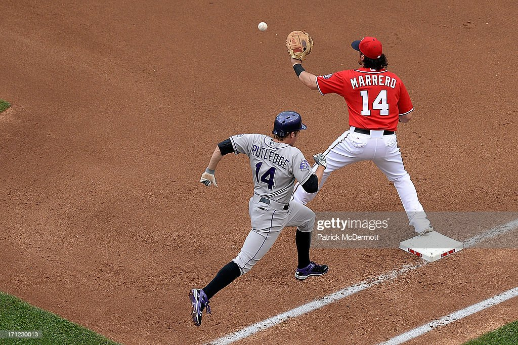 <a gi-track='captionPersonalityLinkClicked' href=/galleries/search?phrase=Chris+Marrero&family=editorial&specificpeople=712968 ng-click='$event.stopPropagation()'>Chris Marrero</a> #14 of the Washington Nationals makes a catch at first base as <a gi-track='captionPersonalityLinkClicked' href=/galleries/search?phrase=Josh+Rutledge&family=editorial&specificpeople=9541486 ng-click='$event.stopPropagation()'>Josh Rutledge</a> #14 of the Colorado Rockies is out on a ground ball to shortstop in the fourth inning during a game at Nationals Park on June 23, 2013 in Washington, DC.