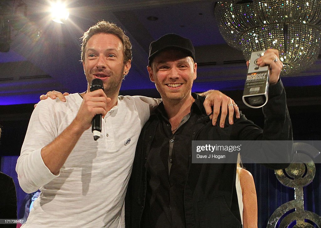 Chris Martin and Jonny Buckland of Coldplay win award for the Royal Albert Hall best British Act at the Nordoff Robbins Silver Clef Award at London Hilton on June 28, 2013 in London, England.
