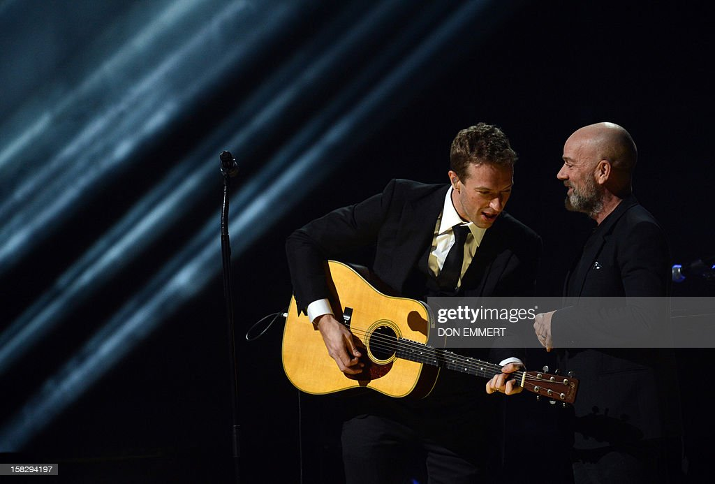 Chris Martin (L) confers with Michael Stipe (R) on stage during '12-12-12 ~ The Concert For Sandy Relief' December 12, 2012 at Madison Square Garden in New York.