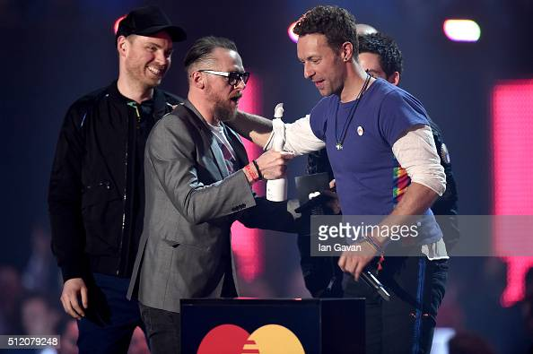 Chris Martin from Coldplay onstage with their Best British Group award with presenter Simon Pegg during the BRIT Awards 2016 at The O2 Arena on...