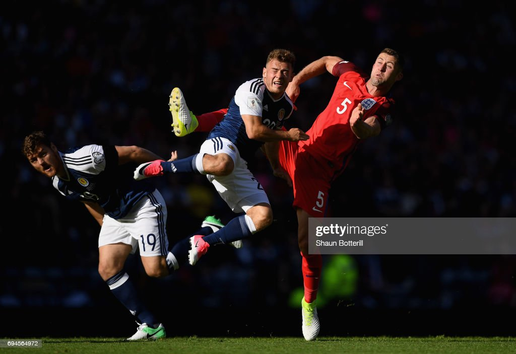 Chris Martin of Scotland and Ryan Fraser of Scotland battle for possession with Gary Cahill of England during the FIFA 2018 World Cup Qualifier between Scotland and England at Hampden Park National Stadium on June 10, 2017 in Glasgow, Scotland.
