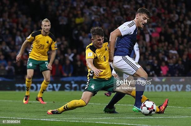 Chris Martin of Scotland vies with Edvinas Girdvainis of Lithuania during the FIFA 2018 World Cup Qualifier between Scotland and Lithuania at Hampden...