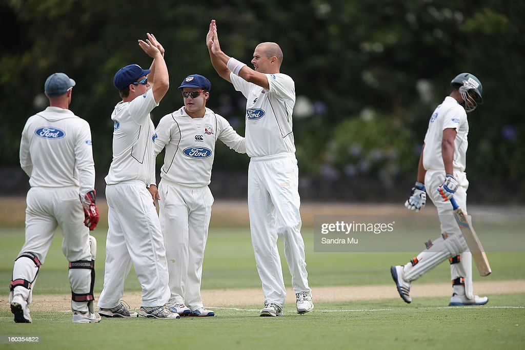 Chris Martin of the Aces (C) celebrates the wicket of Jeet Raval of the Stags on day one of the Plunket Shield match between the Auckland Aces and the Central Stags January 30, 2013 in Auckland, New Zealand.