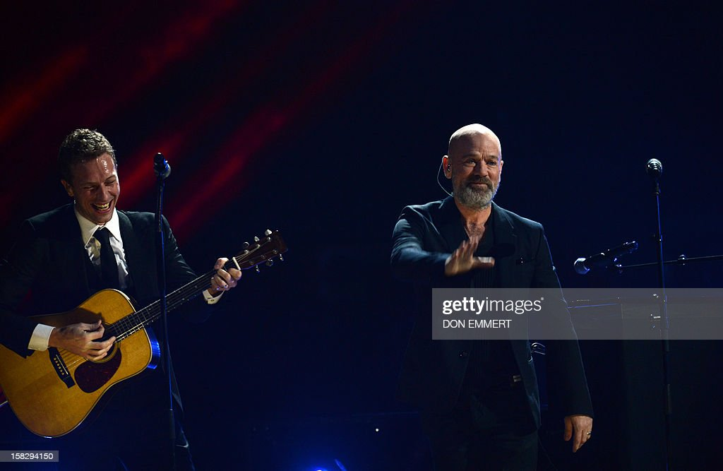 Chris Martin (L) performs as Michael Stipe (R) waves on stage during '12-12-12 ~ The Concert For Sandy Relief' December 12, 2012 at Madison Square Garden in New York.