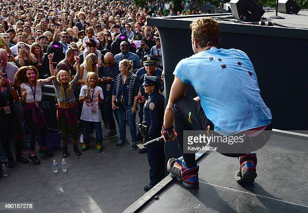 Chris Martin performs with Coldplay onstage while Apple Martin and Moses Martin watch from the crowd during 2015 Global Citizen Festival to end...
