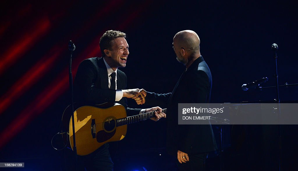 Chris Martin (L) shakes hands with Michael Stipe (R) on stage during '12-12-12 ~ The Concert For Sandy Relief' December 12, 2012 at Madison Square Garden in New York.