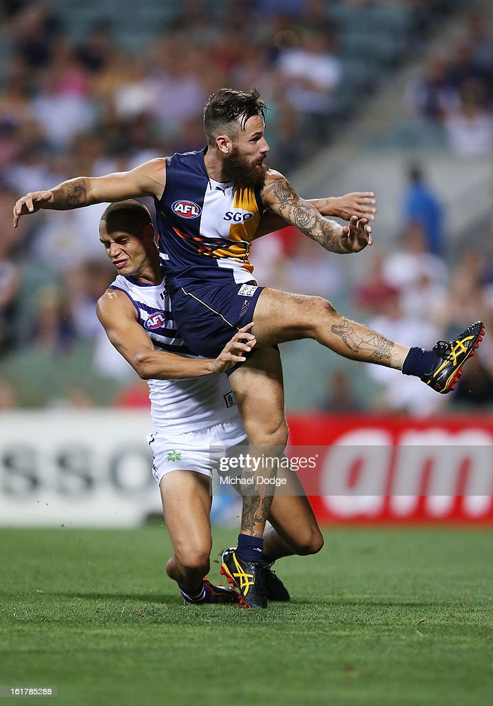 Chris Masten of the West Coast Eagles kicks the ball away from Michael Johnson of the Fremantle Dockers during the round one NAB Cup match between the West Coast Eagles and the Fremantle Dockers at Patersons Stadium on February 16, 2013 in Perth, Australia.