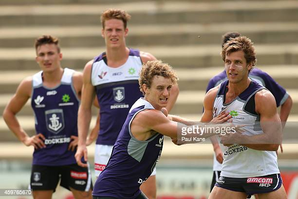 Chris Mayne of the Dockers pushes off Matt De Boer as team mates look on during a Fremantle Dockers AFL preseason training session at Fremantle Oval...