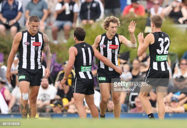 Chris Mayne of the Magpies is congratulated by his teammates after kicking a goal during the 2017 JLT Community Series AFL match between the Richmond...