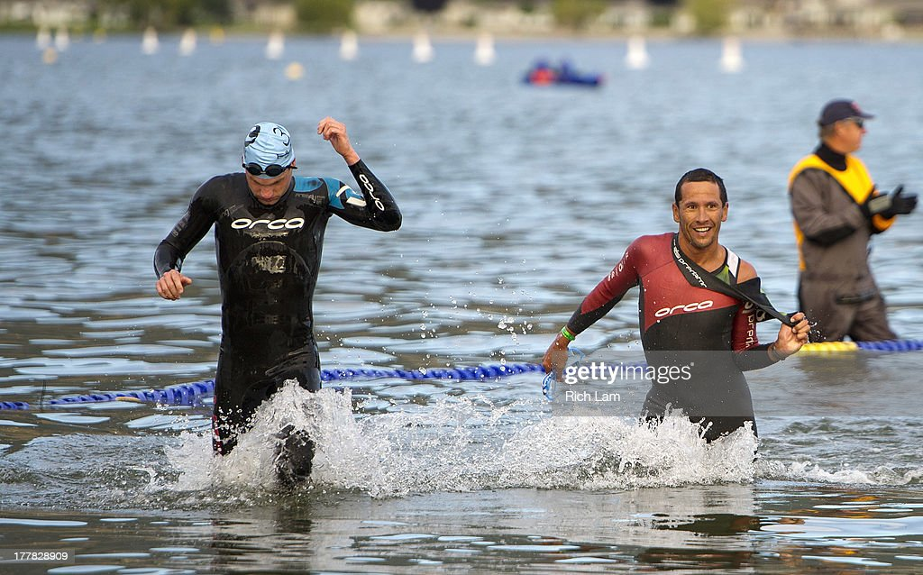 Chris McCormack (right) and Jeff Symonds exit the water after completing the swim portion of the Challenge Penticton Triathlon on August 25, 2013 in Penticton, British Columbia, Canada.