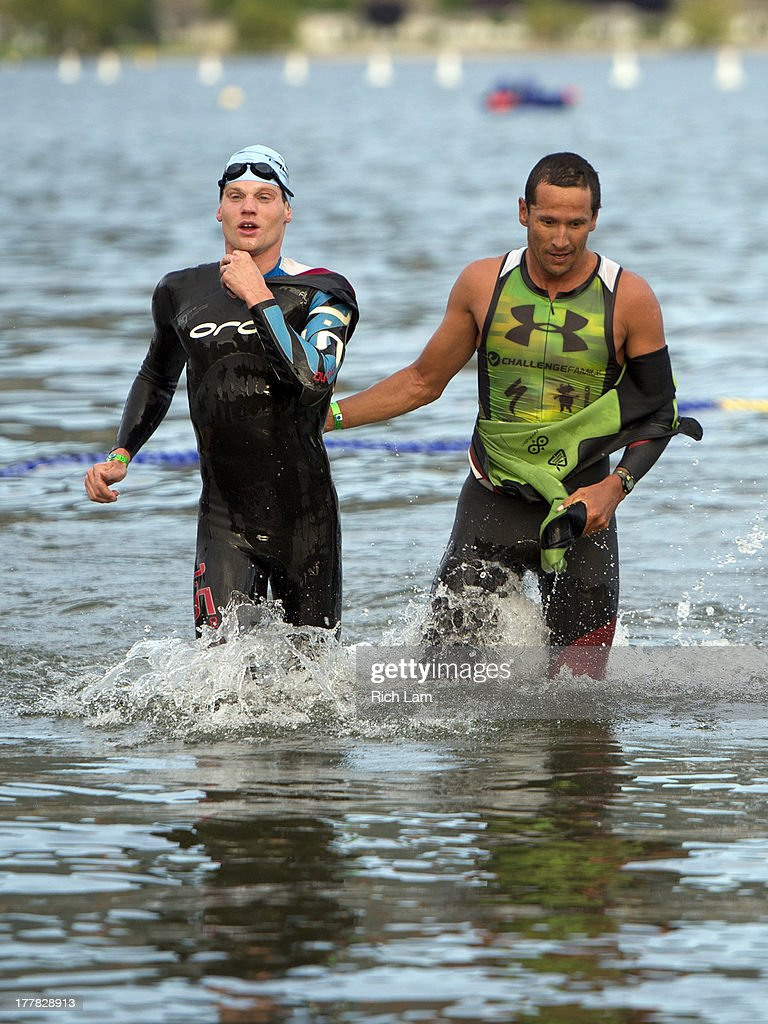 Chris McCormack (right) gives Jeff Symonds a pat on the back as they exit the water after completing the swim portion of the Challenge Penticton Triathlon on August 25, 2013 in Penticton, British Columbia, Canada.