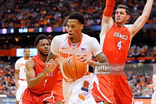 Chris McCullough of the Syracuse Orange controls the ball between Darryl Smith of the Cornell Big Red and Dave LaMore of the Cornell Big Red during...