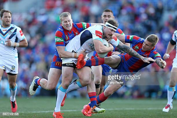 Chris McQueen of the Titans is tackled by the Knights defence during the round 24 NRL match between the Newcastle Knights and the Gold Coast Titans...