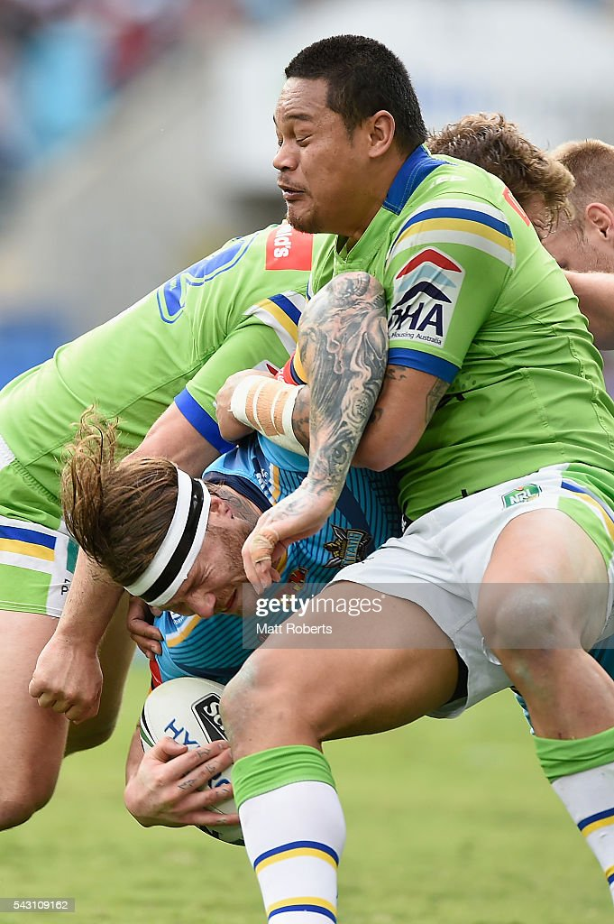 <a gi-track='captionPersonalityLinkClicked' href=/galleries/search?phrase=Chris+McQueen&family=editorial&specificpeople=6128756 ng-click='$event.stopPropagation()'>Chris McQueen</a> of the Titans is tackled during the round 16 NRL match between the Gold Coast Titans and the Canberra Raiders at Cbus Super Stadium on June 26, 2016 in Gold Coast, Australia.