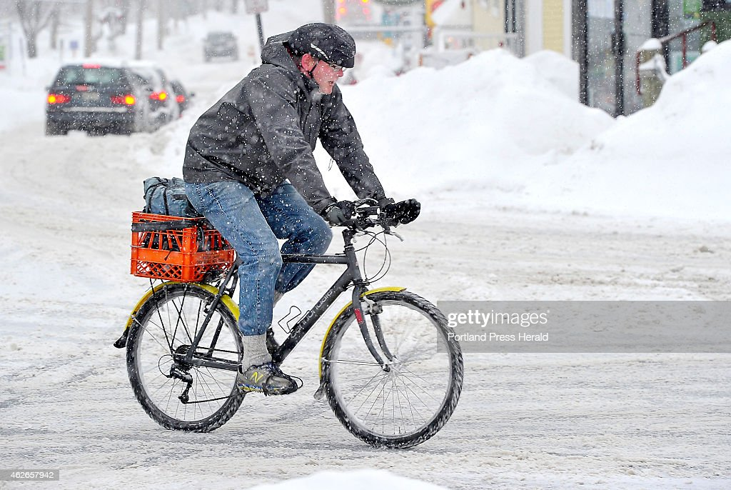 Chris Mills braves the heavy snow as he rides his knobby tired bike along Main Street in Freeport on his way to work at the Bike Boat and Ski retail...