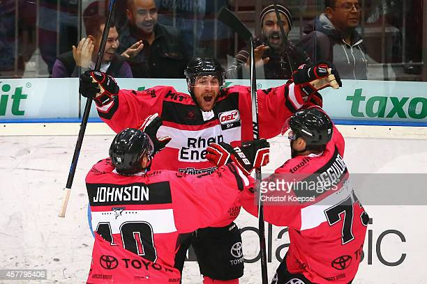 Chris Minard of Koelner Haie celebrates the decision second goal with Jamie Johnson and Mike Iggulden of Koelner Haie during the DEL Ice Hockey match...