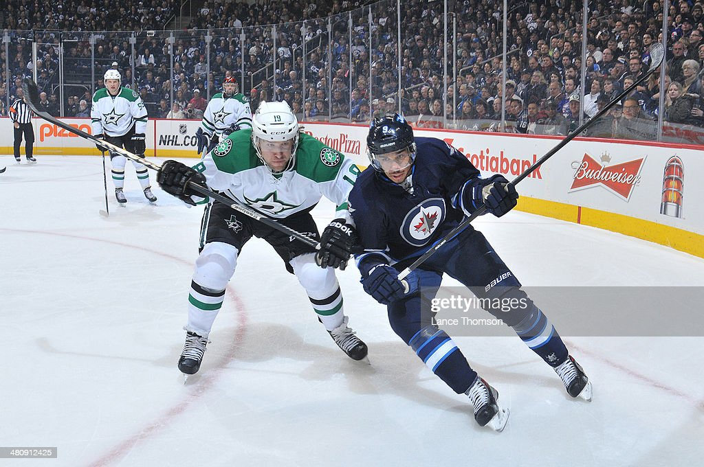 Chris Mueller of the Dallas Stars and Evander Kane of the Winnipeg Jets chase the loose puck towards the boards during first period action at the MTS...