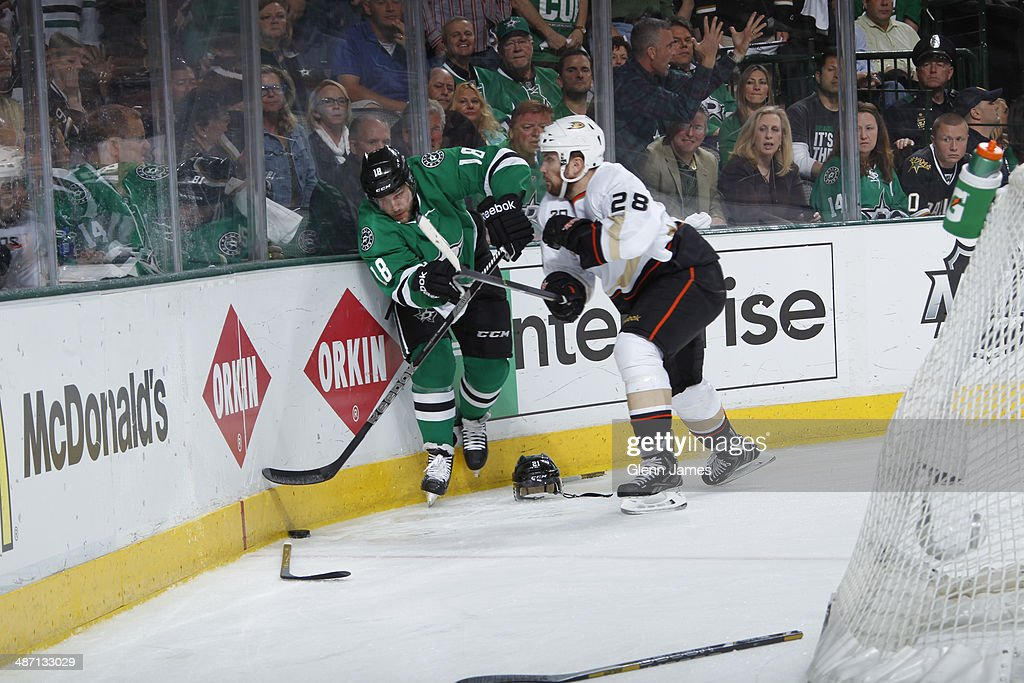 Chris Mueller of the Dallas Stars battles for possession of the puck among a scattering of broken sticks and helmets against Mark Fistric of the...