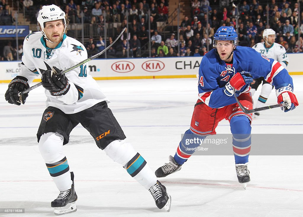 Chris Mueller of the New York Rangers and Andrew Desjardins of the San Jose Sharks race for the puck at Madison Square Garden on October 19 2014 in...