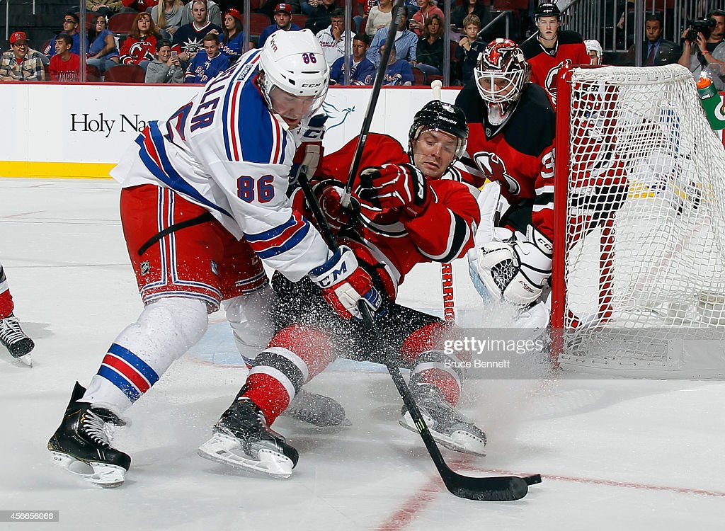 Chris Mueller of the New York Rangers attempts to get past Andy Greene of the New Jersey Devils during the third period at the Prudential Center on...