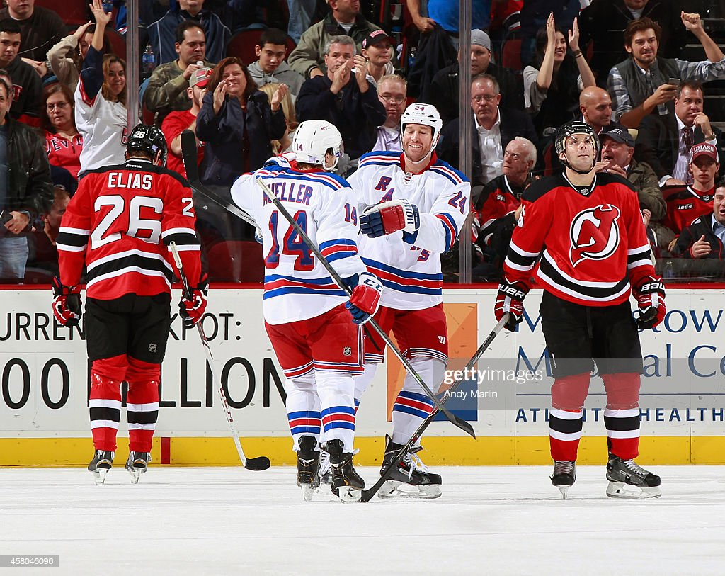 Chris Mueller of the New York Rangers is congratulated by Ryan Malone after scoring a goal as Patrik Elias and Andy Greene of the New Jersey Devils...