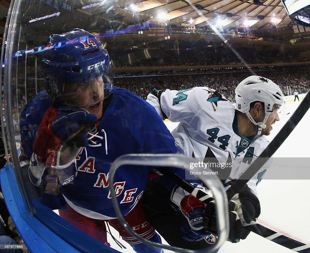 Chris Mueller of the New York Rangers is hit into the boards by MarcEdouard Vlasic of the San Jose Sharks at Madison Square Garden on October 19 2014...