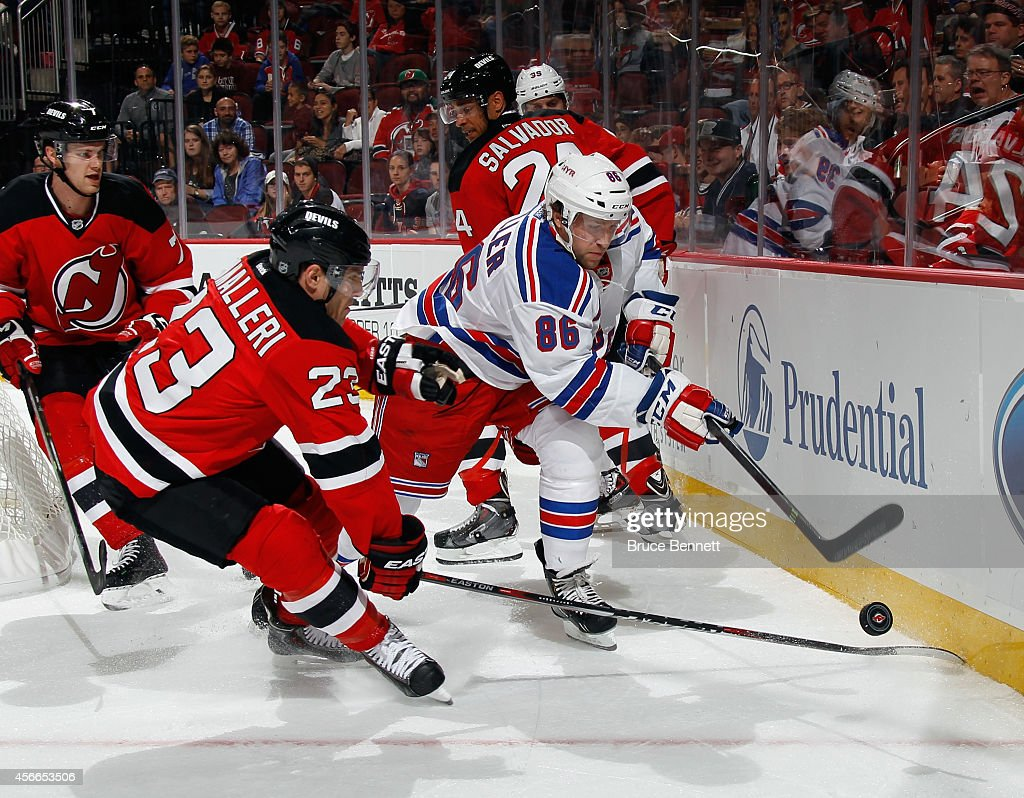 Chris Mueller of the New York Rangers moves the puck around Mike Cammalleri of the New Jersey Devils during the first period at the Prudential Center...