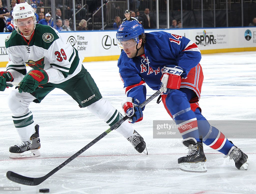 Chris Mueller of the New York Rangers skates with the puck against Nate Prosser of the Minnesota Wild at Madison Square Garden on October 27 2014 in...