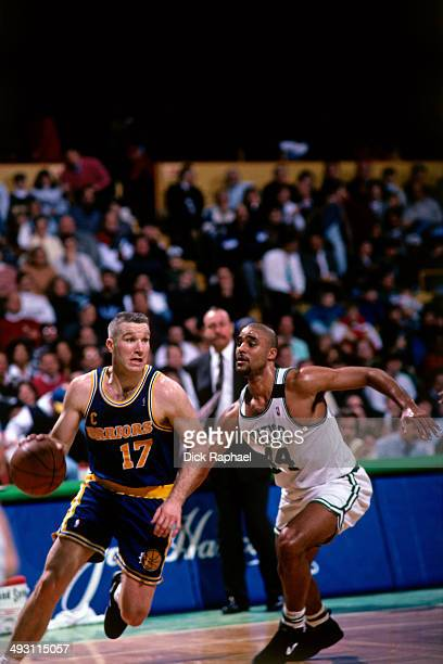 Chris Mullin of the Golden State Warriors drives against Rick Fox of the Boston Celtics during a game played at the Boston Garden in Boston...