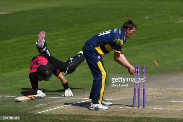 Chris Nash of Sussex dives to make his ground as Michael Hogan of Glamorgan breaks the stumps during the Royal London OneDay Cup match between Sussex...