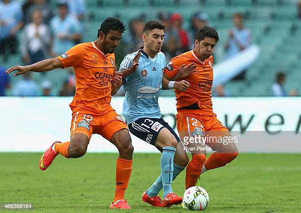 Chris Naumoff of Sydney FC is tackled by Jean Carlos Solorzano and Dimitri Petratos of the Roar during the round 21 ALeague match between Sydney FC...