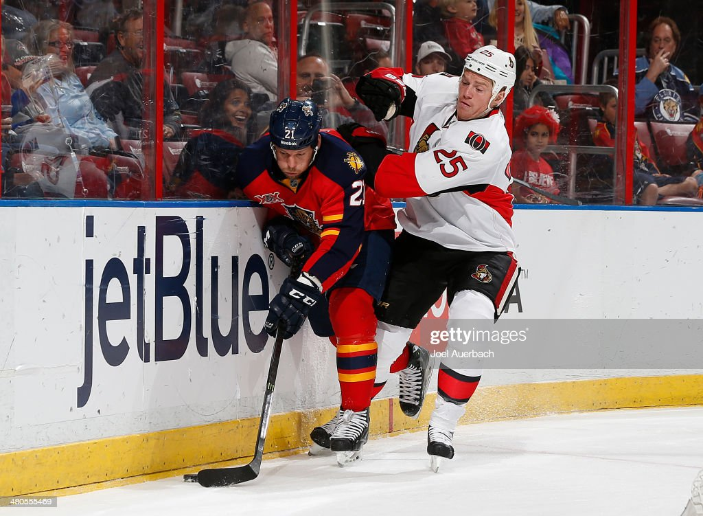 Chris Neil of the Ottawa Senators and Krys Barch of the Florida Panthers fight for control of the puck along the boards at the BBT Center on March 25...