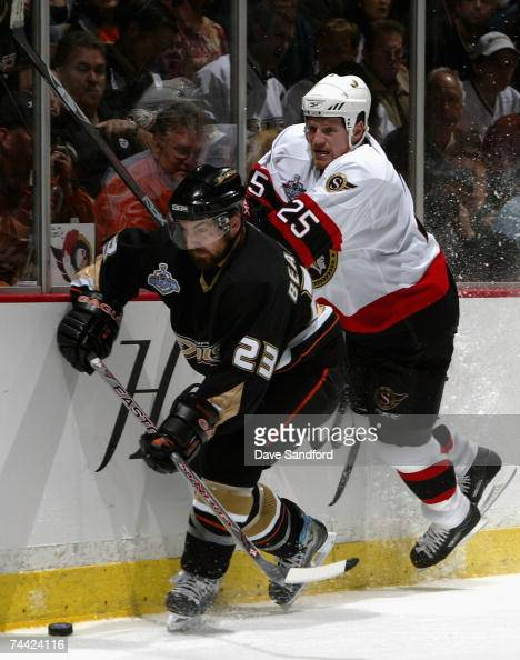 Chris Neil of the Ottawa Senators attempts to check Francois Beauchemin of the Anaheim Ducks off the puck during the first period of Game Five of the...