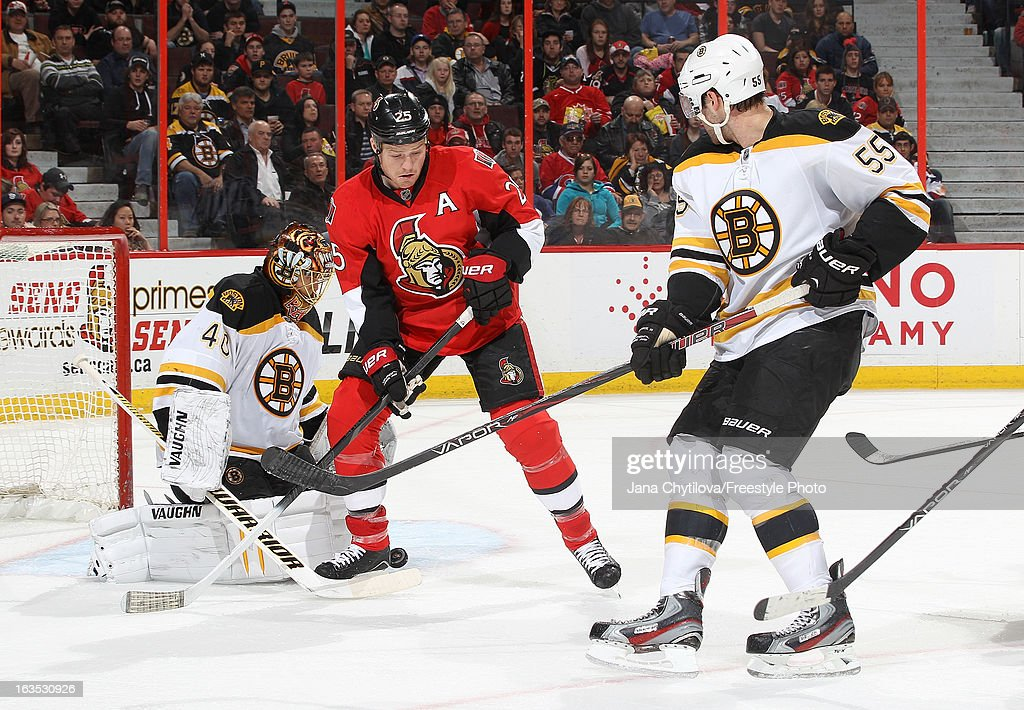 Chris Neil #25 of the Ottawa Senators attempts to get the rebound in front of Tuukka Rask #40 of the Boston Bruins, as Johnny Boychuk #55 of the Boston Bruins looks on, during an NHL game at Scotiabank Place, on March 11, 2013 in Ottawa, Ontario, Canada.