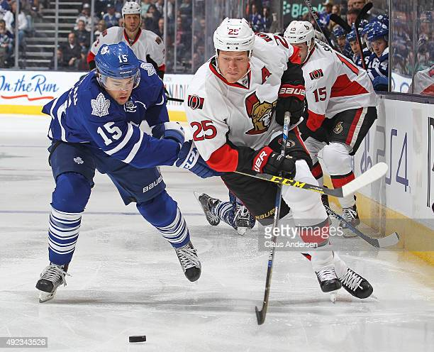 Chris Neil of the Ottawa Senators battles against PA Parenteau of the Toronto Maple Leafs during an NHL game at the Air Canada Centre on October 10...