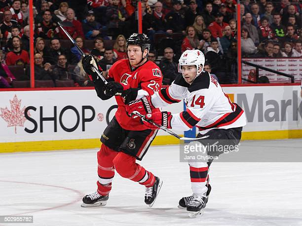 Chris Neil of the Ottawa Senators battles for position against Adam Henrique of the New Jersey Devils at Canadian Tire Centre on December 30 2015 in...