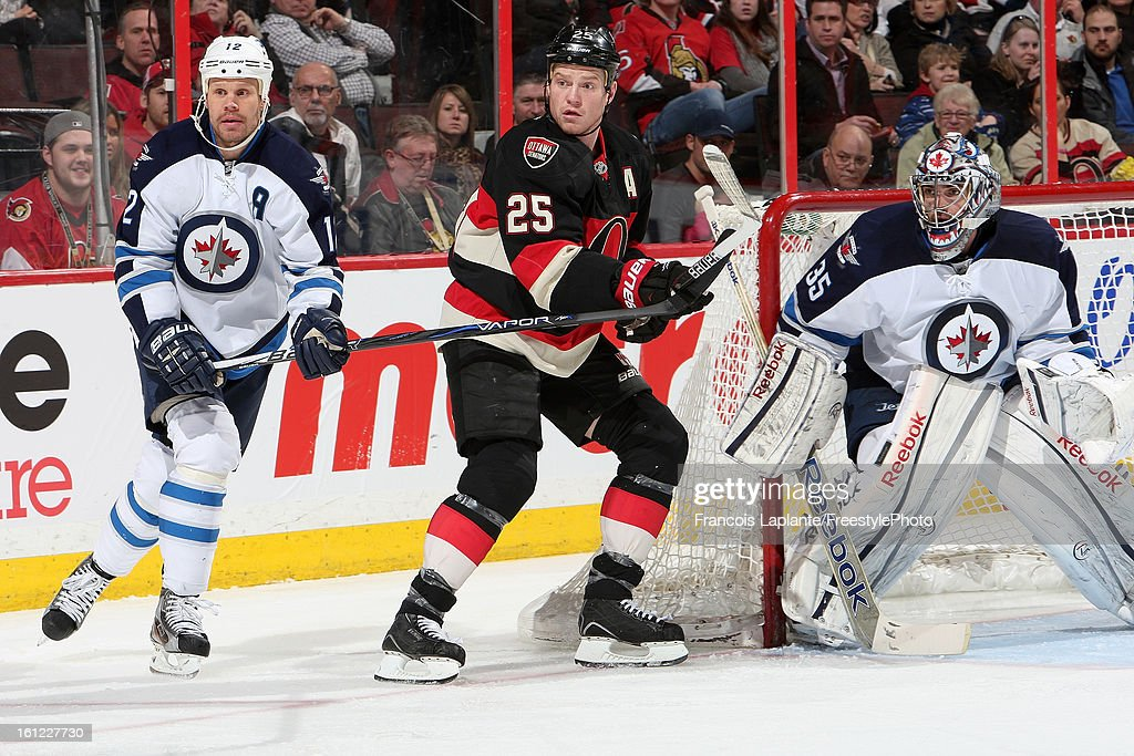 Chris Neil #25 of the Ottawa Senators battles for position against <a gi-track='captionPersonalityLinkClicked' href=/galleries/search?phrase=Olli+Jokinen&family=editorial&specificpeople=202946 ng-click='$event.stopPropagation()'>Olli Jokinen</a> #12 of the Winnipeg Jets as <a gi-track='captionPersonalityLinkClicked' href=/galleries/search?phrase=Al+Montoya&family=editorial&specificpeople=213916 ng-click='$event.stopPropagation()'>Al Montoya</a> #35 looks on the play during an NHL game at Scotiabank Place on February 9, 2013 in Ottawa, Ontario, Canada.