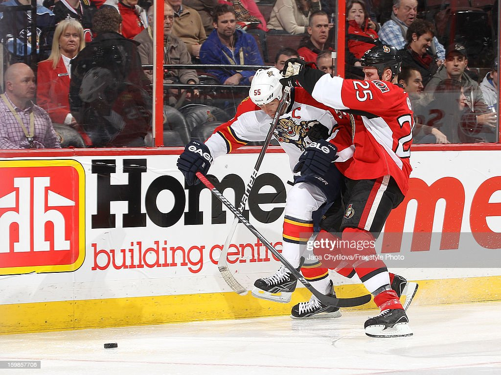 Chris Neil #25 of the Ottawa Senators battles for the loose puck against <a gi-track='captionPersonalityLinkClicked' href=/galleries/search?phrase=Ed+Jovanovski&family=editorial&specificpeople=203147 ng-click='$event.stopPropagation()'>Ed Jovanovski</a> #55 of the Florida Panthers during an NHL game at Scotiabank Place on January 21, 2013 in Ottawa, Ontario, Canada.