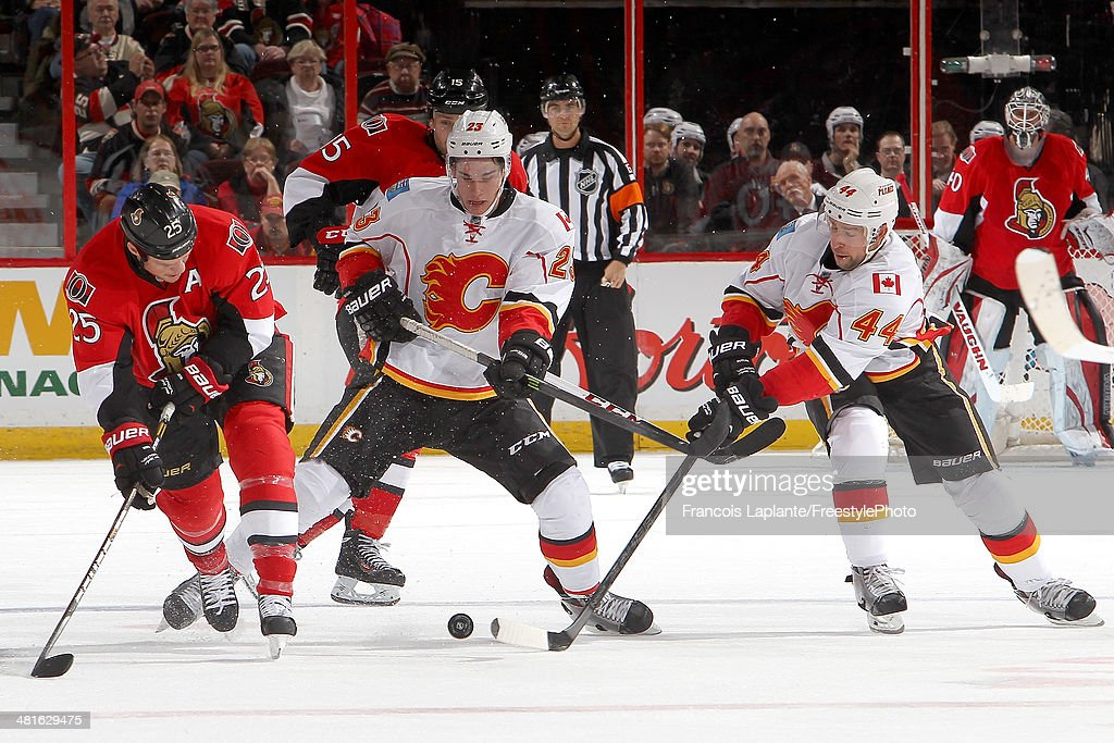 Chris Neil #25 of the Ottawa Senators battles for the puck at centre ice against Sean Monahan #23 and Chris Butler #44 of the Calgary Flames during an NHL game at Canadian Tire Centre on March 30, 2014 in Ottawa, Ontario, Canada.