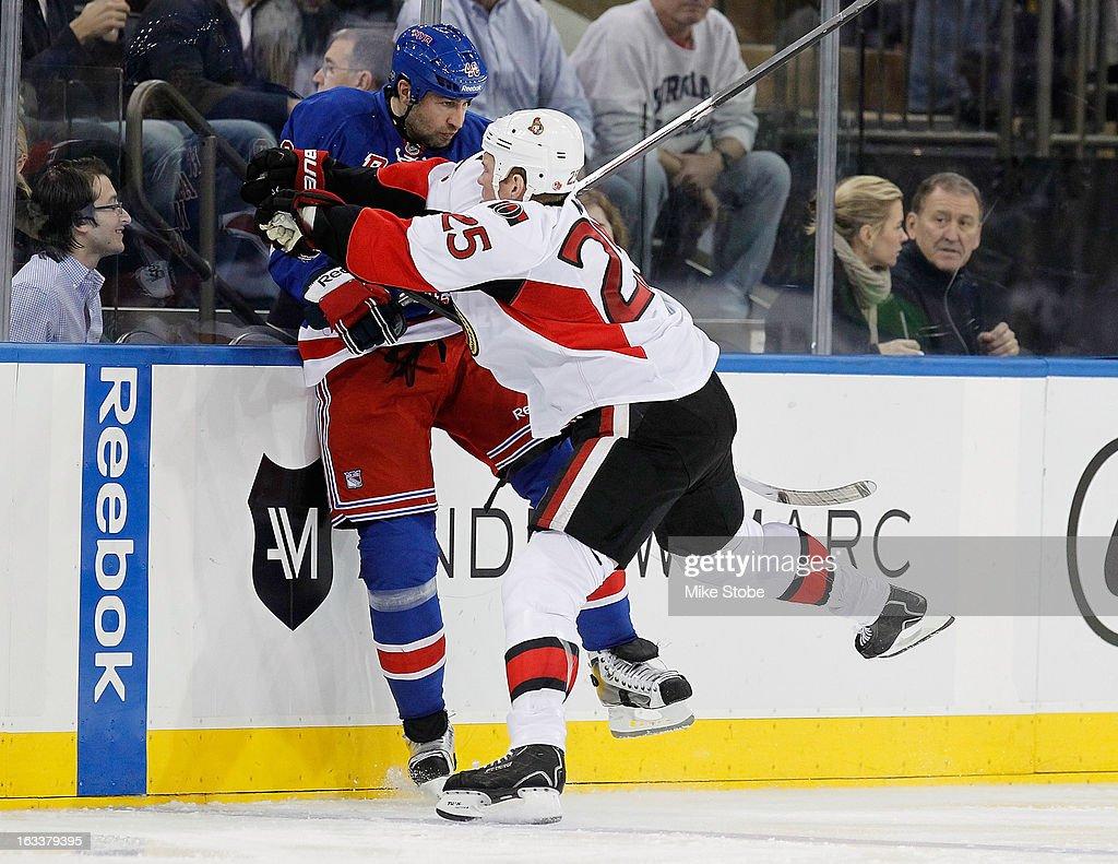 Chris Neil #25 of the Ottawa Senators cehcks Roman Hamrlik #40 of the New York Rangers into the boards at Madison Square Garden on March 8, 2013 in New York City. Senators defeated the Rangers 3-2.