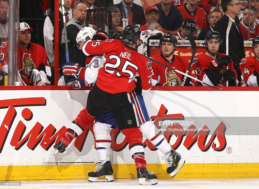 Chris Neil #25 of the Ottawa Senators checks Michael Ryder #73 of the Montreal Canadiens along the boards in Game Four of the Eastern Conference Quarterfinals during the 2013 NHL Stanley Cup Playoffs, at Scotiabank Place, on May 7, 2013 in Ottawa, Ontario, Canada.