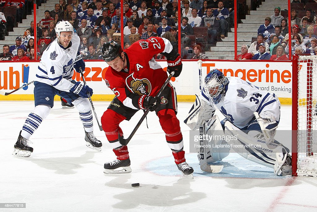 Chris Neil #25 of the Ottawa Senators controls a rebound against James Reimer #34 of the Toronto Maple Leafs as Cody Franson #4 defends on April 12, 2014 at Canadian Tire Centre in Ottawa, Ontario, Canada.