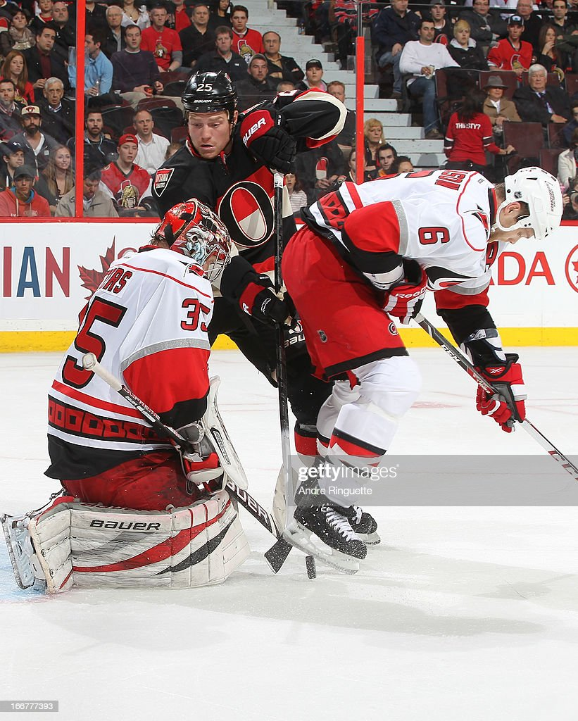 Chris Neil #25 of the Ottawa Senators digs for the loose puck on a rebound against Justin Peters #35 and <a gi-track='captionPersonalityLinkClicked' href=/galleries/search?phrase=Tim+Gleason&family=editorial&specificpeople=211575 ng-click='$event.stopPropagation()'>Tim Gleason</a> #6 of the Carolina Hurricanes on April 16, 2013 at Scotiabank Place in Ottawa, Ontario, Canada.