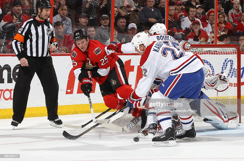 Chris Neil #25 of the Ottawa Senators falls as he passes the puck past <a gi-track='captionPersonalityLinkClicked' href=/galleries/search?phrase=Tomas+Kaberle&family=editorial&specificpeople=202238 ng-click='$event.stopPropagation()'>Tomas Kaberle</a> #22 of the Montreal Canadiens during an NHL game at Scotiabank Place on January 30, 2013 in Ottawa, Ontario, Canada.